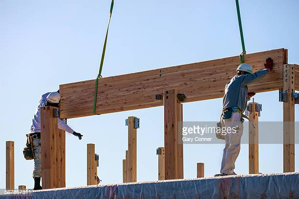 Construction workers guide beam