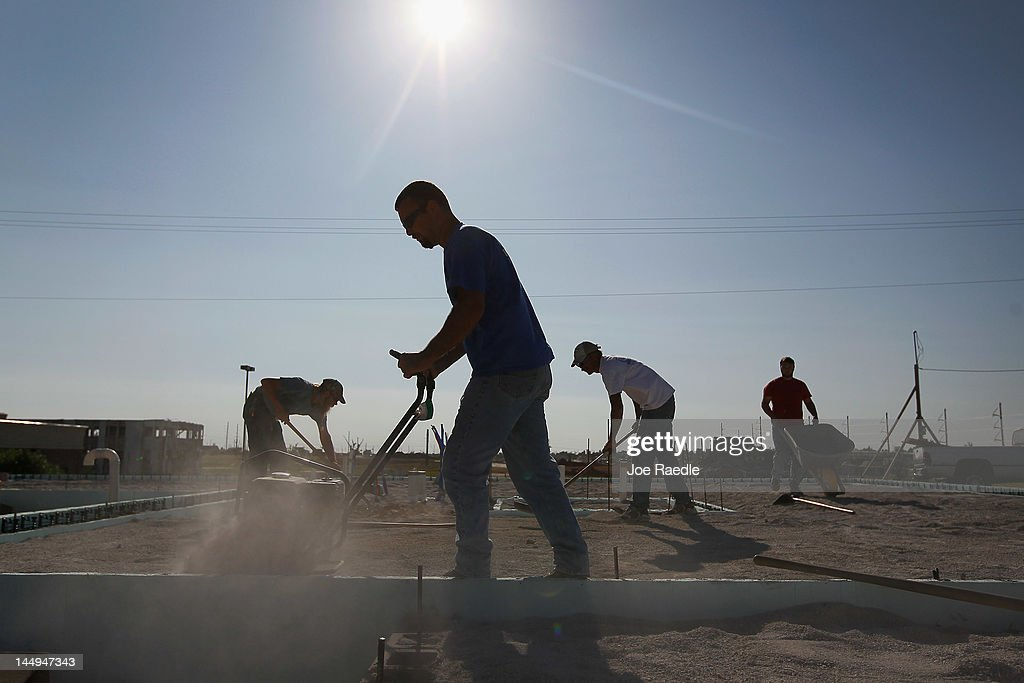 Construction workers help build a home on the spot where a home had been knocked down almost one year ago by the massive tornado that passed through...