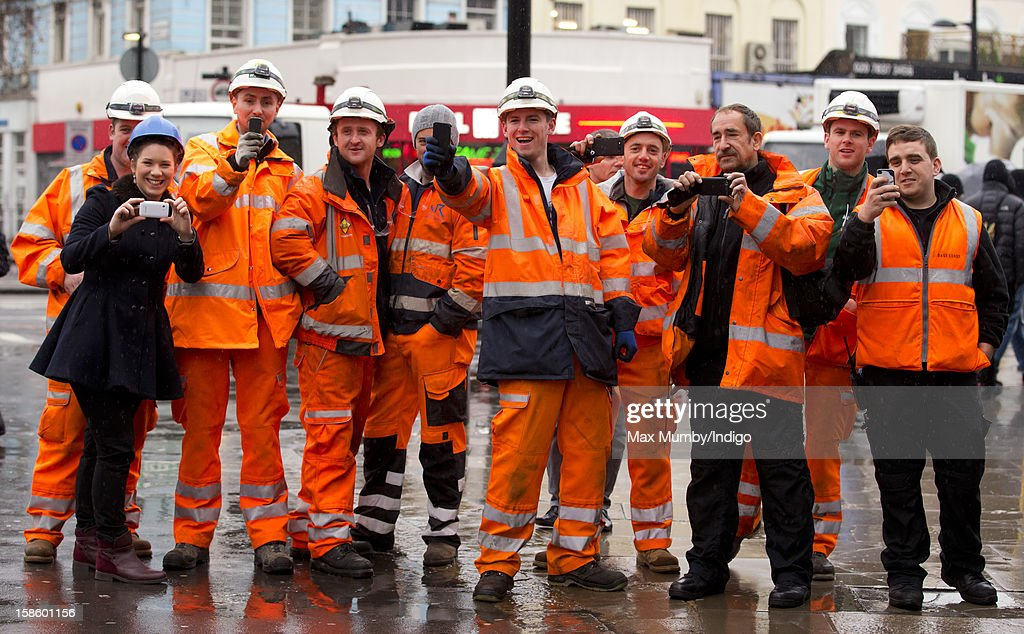 Construction workers hold up their camera phones after watching Queen Elizabeth II and Prince Philip, Duke of Edinburgh arrive at King's Cross Railway Station to take the train to King's Lynn on route to her Norfolk Estate, Sandringham House, for her traditional Christmas Break on December 20, 2012 in London, England.