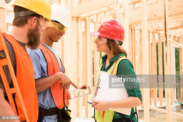 Construction workers inside job site using digital tablet.