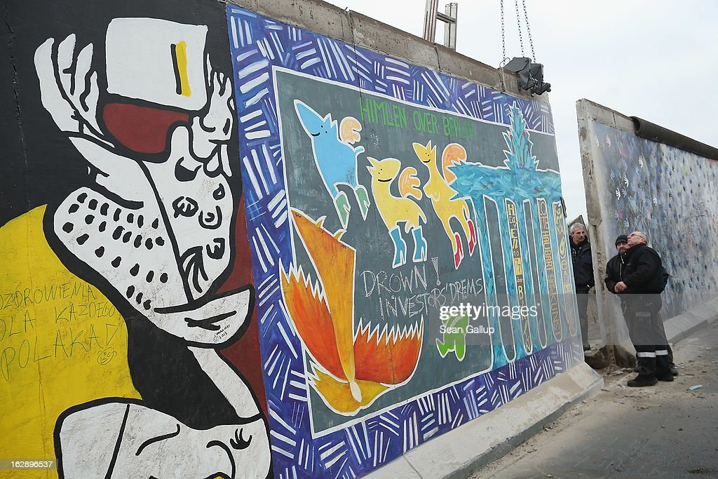 Construction workers inspect a section of the East Side Gallery, which is the longest still-standing portion of the former Berlin Wall, before attempting to remove it with a crane on March 01, 2013 in Berlin, Germany. A real estate developer is planning to build a 14-storey apartment building between the Wall and the Spree River and needs to remove a 25-meter long Wall section in order to allow access to the construction site. Critics, including East Side Gallery mural artists and Spree River embankment development opponents, decry the move, citing the importance of the East Side Gallery's status as a protected landmark and a major tourist attraction. The East Side Gallery is approximately 1.3 kilometers long.