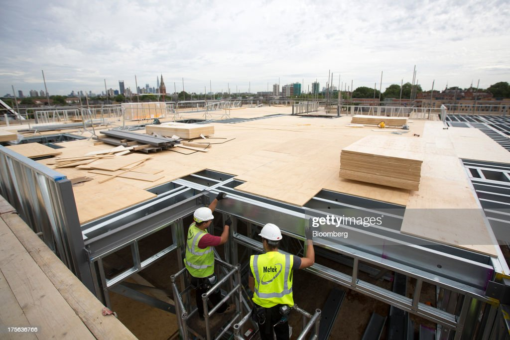 Construction workers inspect support beams at the Oval Quarter, a shared ownership, private and social residential housing complex developed by Higgins Group Plc in partnership with Nottinghill Housing and Pinnacle Regeneration Group, in London, U.K., on Monday, Aug. 5, 2013. U.K. house prices rose 0.8 percent in July, from 0.3 percent the previous month, Nationwide Building Society said. Photographer: Simon Dawson/Bloomberg via Getty Images