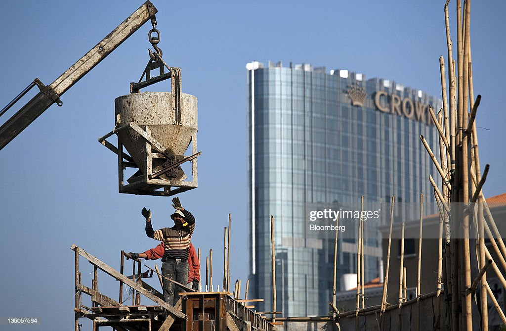 Construction workers labor on a wall as Melco Crown Entertainment Ltd.'s Crown Towers hotel stands behind it in Macau, China, on Sunday, Dec. 4, 2011. Macau casino gambling revenue climbed a better-than-expected 33 percent last month as economic growth stoked demand from visitors from China's mainland. Photographer: Jerome Favre/Bloomberg via Getty Images