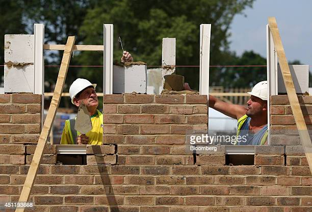 Construction workers lay bricks around window apertures for a new home under construction at a Crest Nicholson Holdings Plc residential housing...