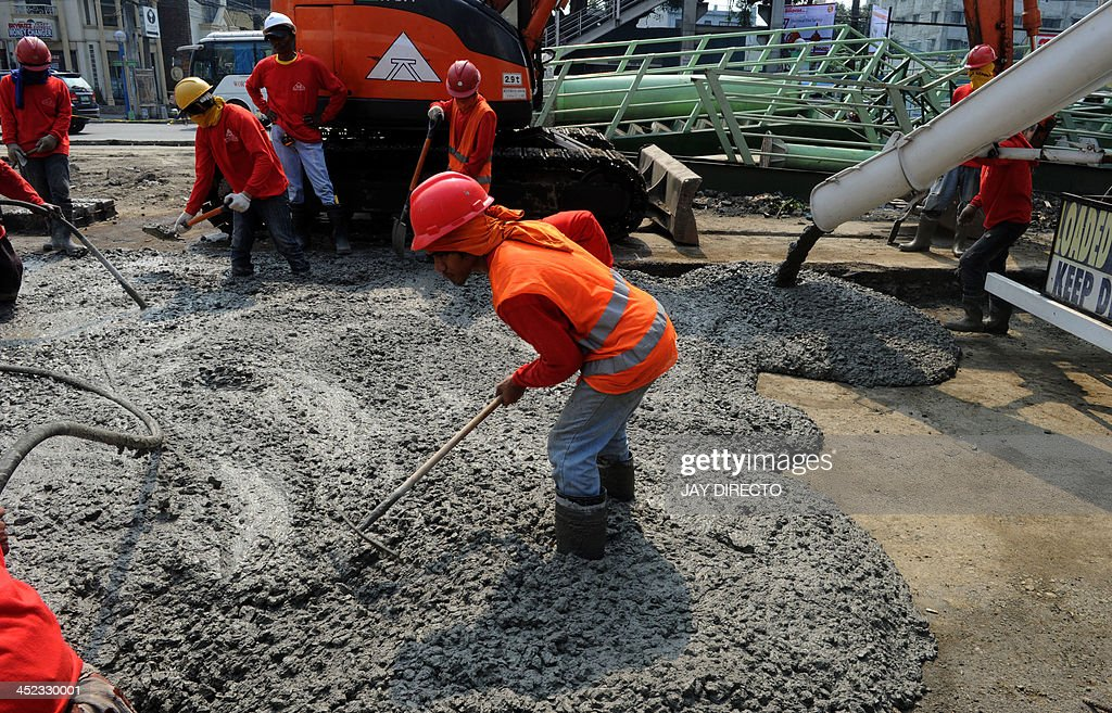 Construction workers lay concrete for a road in Manila on November 28, 2013. The Philippines economy is expected to grow about seven percent in 2013, as expansion in October-December is stunted by this month's devastating typhoon, the government said on November 28. AFP PHOTO / Jay DIRECTO
