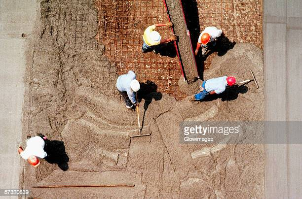Construction workers lay concrete, shot from above