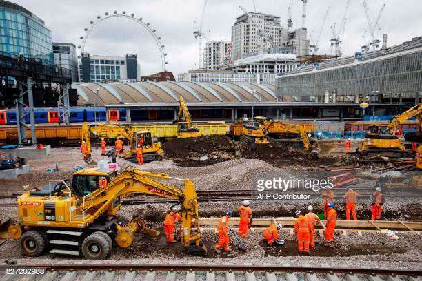 Construction workers lay rail tracks as Network Rail commences major work to upgrade London Waterloo rail station in central London on August 7 2017...