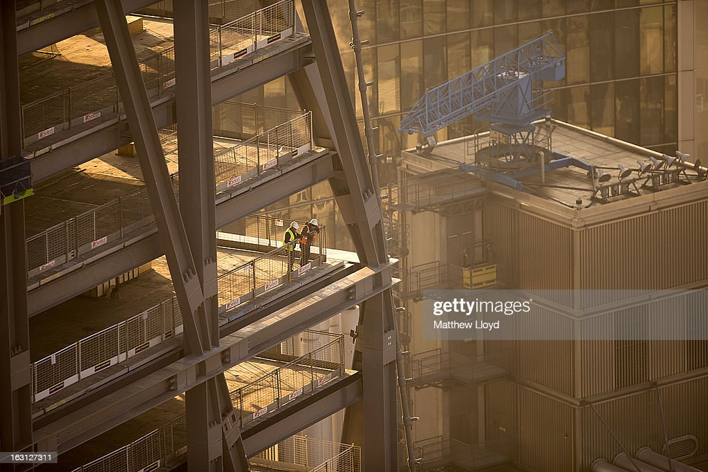 Construction workers look over a ledge in the 122 Leadenhall St skyscraper, nicknamed the Cheesegrater, at sunrise on March 5, 2013 in London, England. The recent construction of numerous tall buildings on the London skyline has been controversial due to concerns that views of historic landmark buildings, such as St Paul's cathedral, are being obscured.