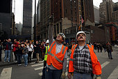 Construction workers look up at scaffold carrying two workers hanging 69 floors up at One World Trade Center on November 12 2014 in New York City The...
