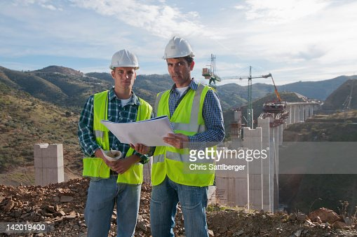 Construction workers looking at blueprint at construction site : Stock Photo