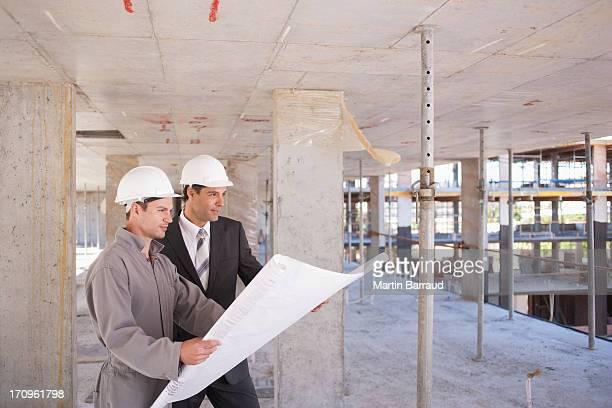 Trabajadores de la construcción mirando blueprints en solar de construcción