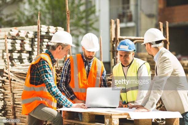 Construction workers looking at laptop on construction site