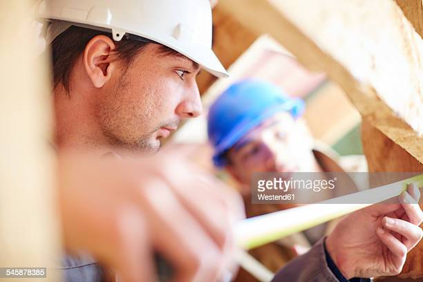 Construction workers measuring roof beams