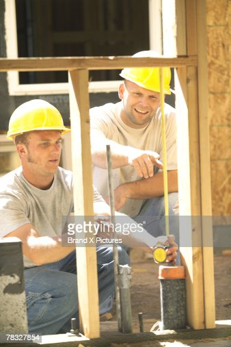 Construction workers measuring window : Stock Photo