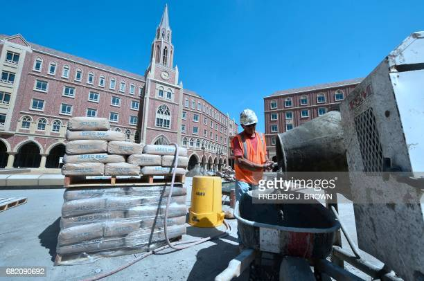 Construction workers mix cement at the University of Southern California which will play host to the Main Press Center as the IOC Evaluation...