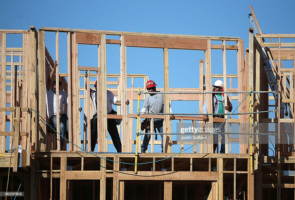 Construction workers move a framed wall into place at a new housing development on February 20, 2013 in San Mateo, California. The Commerce Department reported that new housing starts dropped 8.5% in January following a 15.7% increase one month earlier.