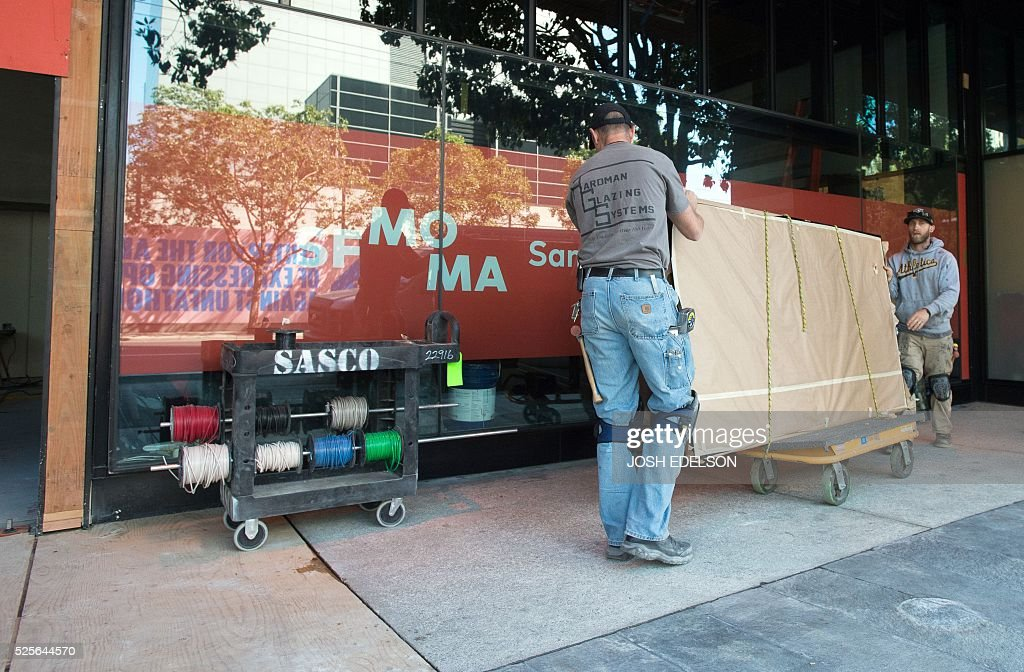 Construction workers move an art piece into the San Francisco Museum of Modern Art (SFMOMA) in San Francisco, California on April 28, 2016. The newly redesigned museum integrates a 10-story expansion in a new building and will open to the public on May 14, 2016. / AFP / Josh Edelson