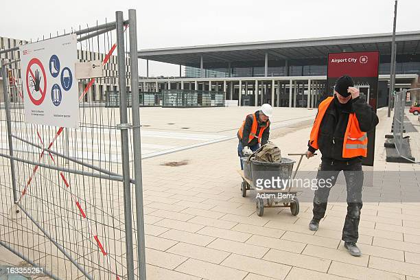 Construction workers move building materials outside the terminal building of the stillunopened Berlin Brandenburg International airport on March 8...