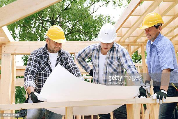 construction workers on a background of a frame house