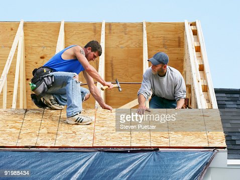 Construction workers on a roof of home : Stock Photo