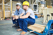 Full length portrait of two builders wearing hardhats taking break from work drinking coffee and resting sitting on pack of wood indoors