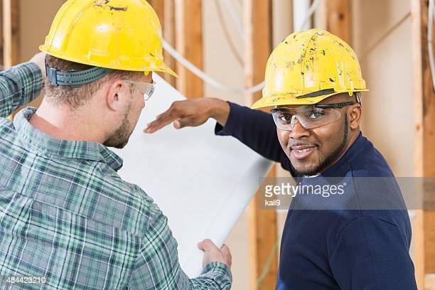 Travailleurs de la Construction au travail site hardhats, avec des plans