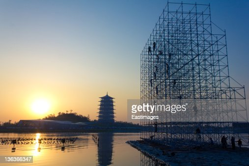 Construction workers on scaffold at sunset : Foto de stock