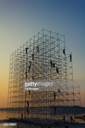 Construction workers on scaffold at sunset : Stock Photo