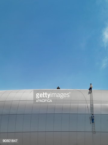 Construction workers on top of a stadium. : Stock Photo