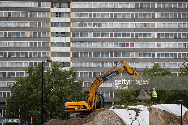 Construction workers operate in front of a residential tower block in an area of Southwark with a high concentration of social housing on August 28...
