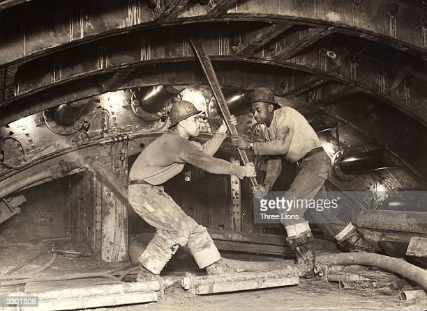 Construction workers or sandhogs working nearly seventy feet below the East River New York tightening the bolts of the cast iron lining of the new...