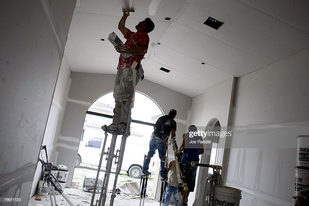 Construction workers paint a room in a house under construction January 17, 2008 in Miami, Florida. The Commerce Department released figures showing that new home construction is down 24.8 percent from 2006.
