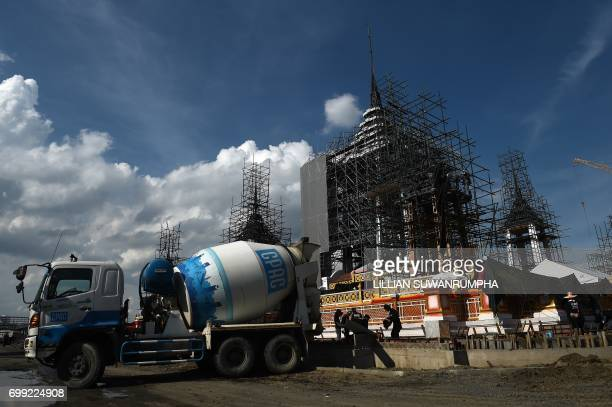 Construction workers pour cement just outside the funeral pyre and surrounding pavilions for the late Thai King Bhumibol Adulyadej inside Sanam Luang...