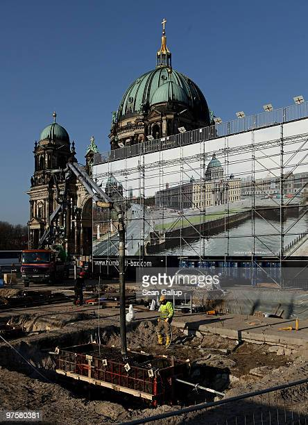 Construction workers pour concrete for the foundations of an informational center about the reconstruction of the Berlin Palace in the city center on...