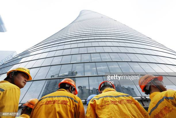 Construction workers prepare to install the final steel beam on the 632meterhigh Shanghai's tallest building on August 3 2014 in Shanghai China The...