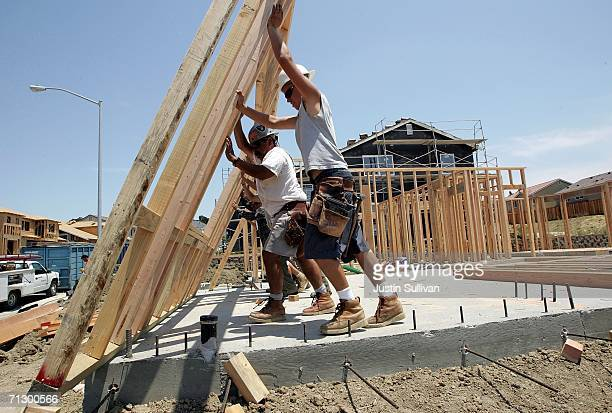 Construction workers raise wood framing as they build homes in a new housing development June 26 2006 in Richmond California A report issued by the...