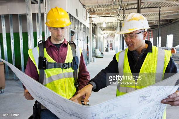 Construction workers reading blueprints at construction site