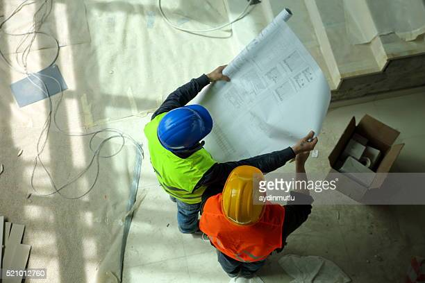 Bau Arbeiter lesen Pläne liegen vor