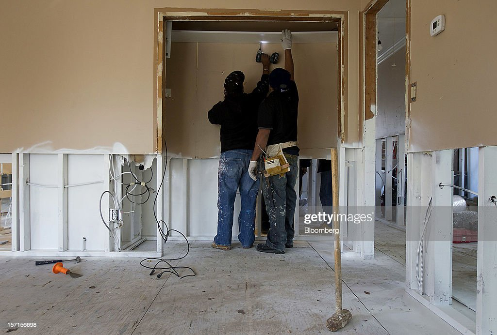 Construction workers repair a home in the Staten Island borough of New York, U.S., on Wednesday, Nov. 28, 2012. Superstorm Sandy is giving the U.S. Northeast, and the rest of the country, an economic boost that may eventually surpass the loss of business it caused. Photographer: Jin Lee/Bloomberg via Getty Images