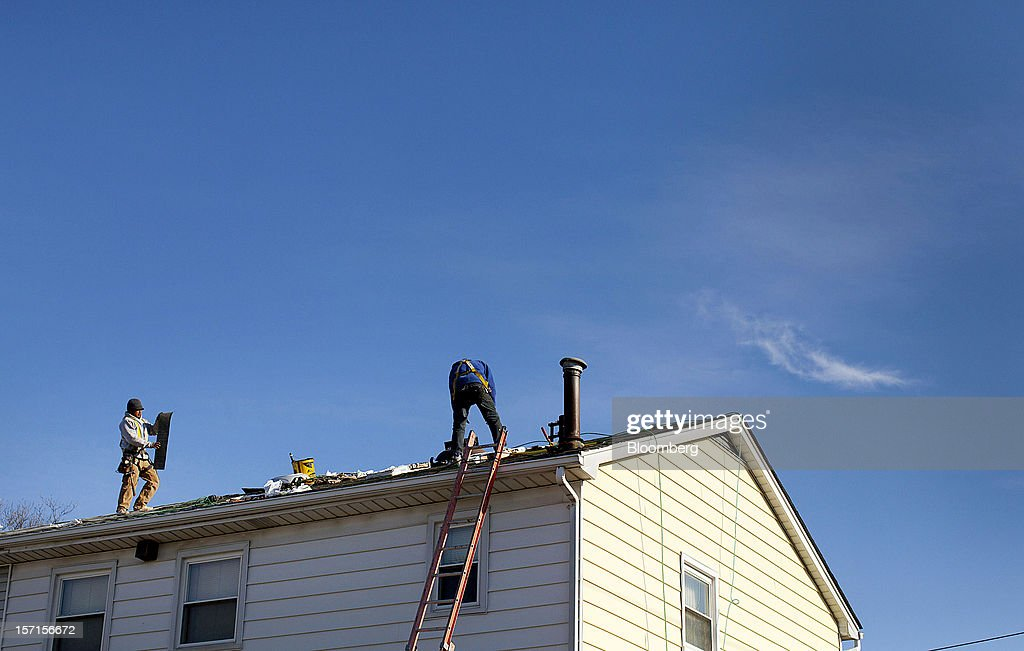 Construction workers repair the roof on a home in the Staten Island borough of New York, U.S., on Wednesday, Nov. 28, 2012. Superstorm Sandy is giving the U.S. Northeast, and the rest of the country, an economic boost that may eventually surpass the loss of business it caused. Photographer: Jin Lee/Bloomberg via Getty Images