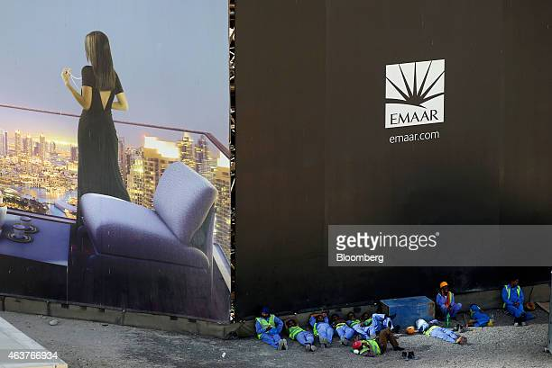 Construction workers rest beneath giant hoardings surrounding an Emaar Properties PJSC construction site in the financial district of Dubai United...