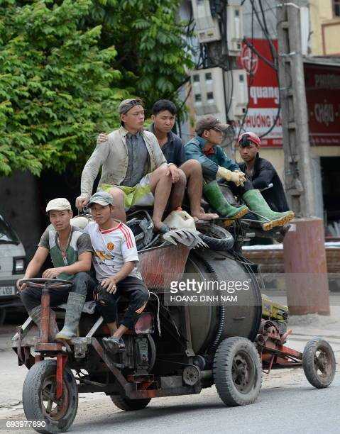 Construction workers ride on a motorised concretmixing machine vehicle as they make way to a construction site in the outskirts of Hanoi on June 9...