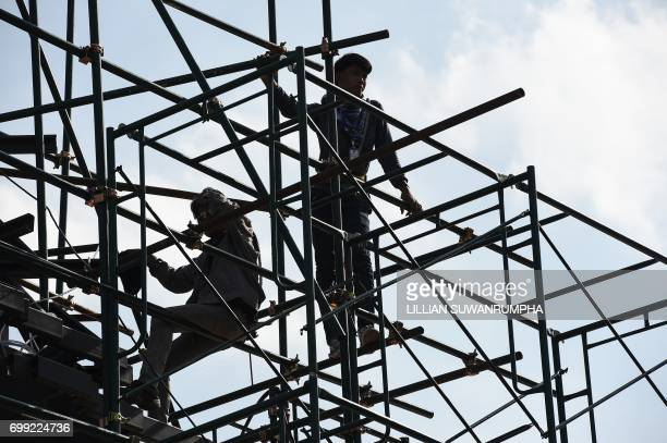 Construction workers scale the scaffolding around the funeral pyre and surrounding pavilions for the late Thai King Bhumibol Adulyadej inside Sanam...