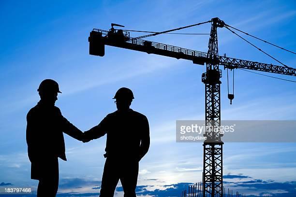 Construction workers shaking hands below crane