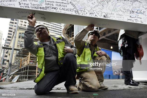 Construction workers sign the final steel beam during a topping off ceremony for the Salesforce Tower in San Francisco California US on Thursday...