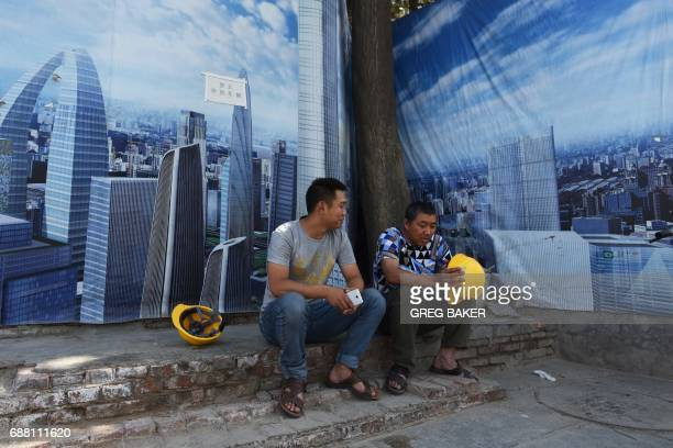 Construction workers sit in front of a billboard outside their construction site in Beijing on May 25 2017 Moody's on May 24 slashed China's credit...