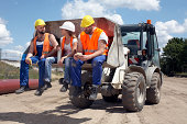3 construction workers sitting on machinery