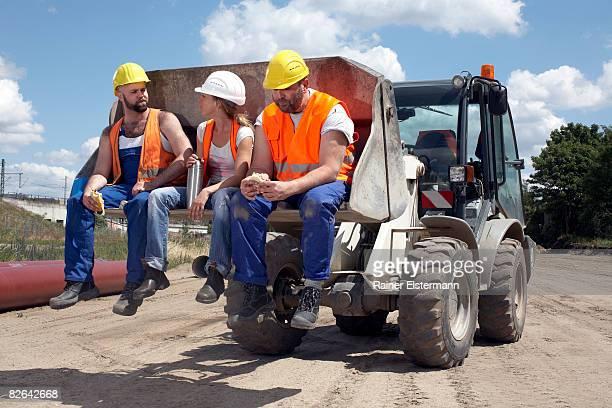 3 Bauarbeitern sitzt auf Maschinen