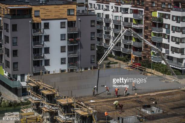 Construction workers smooth concrete on an upper floor structure at the building site for a residential apartment block built by Finep CZ AS in the...