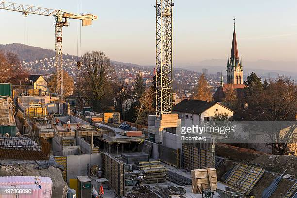 Construction workers stand beneath a crane during the building of new residential property in Zurich Switzerland on Wednesday Nov 11 2015 Risks to...